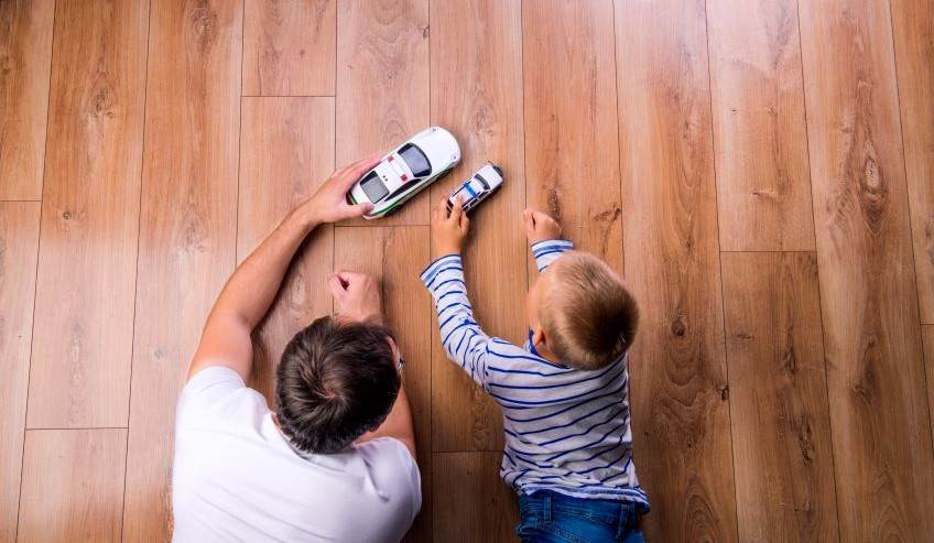 Man and boy playing with toys cars on a wood floor